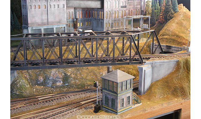 The through truss bridge is coming off a curve at the far right here. The designer has left enough room for the locomotive to straighten out before the loco has to enter the enclosed truss structure. Below the bridge, clearance is tight, so not much of the bridge frame structure hangs very far below rail level of the bridge track.