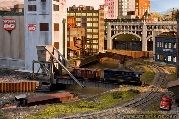 In the Cleveland Flats, we see a B&O H-10 44 crossing a rolling lift bridge with a covered hopper car, the switcher is working the Cargill plant. Also in this scene is a large warehouse (behind the Cargill plant) and a bakery on the far right. In the very back is Downtown Cleveland.