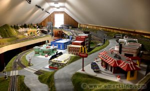 Here's a dramatic view of the Model Railroad Layout just shipped, seen from the center of the layout down to one end. Because the room it fits into is an attic with limited access, the layout had to separate into many small modules.