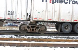 Here is an example of how a Roadrailer is fitted with a railroad truck, while it retains its highway tires, photo Wikimedia.org.