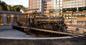A hard day's work at this roundhouse. It must be someplace in Chicago as the distinctive EL train can be seen in the distance. Learn more about this combination HO/O scale layout!