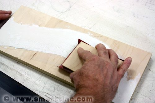 Sand the dried joint compound surface of your road to remove imperfections in preparation for painting