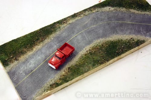 A little sand or fine ballast blends the edges  of the road into the surrounding terrain.