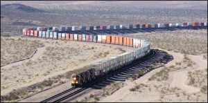 A long BNSF doublestack train is running at track speed through the desert. No fewer than 80 platforms carrying 160 containers are visible in this photo. These trains reach speeds of 70mph, photo wordpress.com