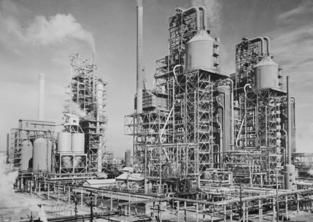 """Photo of an oil refinery, 1944. America's petroleum industries pour out fuel and lubricants for the United Nations. These three new catalytic oil """"cracking"""" units are turning out gasoline for the new machines of war at the plant of a large U.S. refining company in the southern U.S. state of Louisiana. In the eight years of the development of the """"cracking"""" process in producing gasoline, it is estimated that 1,000,000,000 barrels of crude oil have been saved by the oil industry. The """"cracking"""" process subjects crude oil to heat and pressure by which the oil molecules are broken down and made to release more of their derivable elements. The drain of war on such gasoline producing units as these is shown by the fact that the U.S. has manufactured 180,000 planes since December 7, 1941, propelled by gasoline motors. For example, one U.S. Liberator four-motored bomber in a six-hour bombing run consumes 1,800 gallons of gasoline, enough to last the average U.S. civilian motorist from three to five years."""